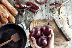 Three large red onions in female hands Stock Photo