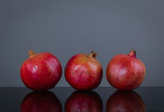 Three large ripe pomegranate on a gray background Royalty Free Stock Photos