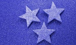 Three large stars on bright red background illuminated Royalty Free Stock Photography