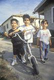 Three Latino children with their scooter, Los Angeles, CA Stock Photography