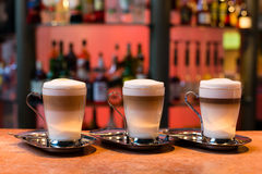 Three latte cups. Three cups of latte on the marble surface Stock Photos