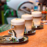 Three latte cups. Three cups of latte on the marble surface Royalty Free Stock Images