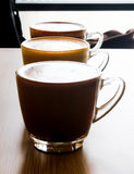 Three latte on a wood table, Art on a Cup of Coffee royalty free stock image