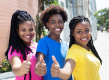 Three laughing african american girlfriends showing thumbs up Royalty Free Stock Photos