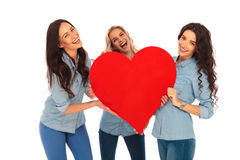 Three laughing casual women holding a big red heart. On white studio background Stock Photo