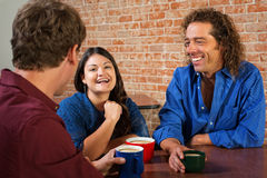 Three Laughing Friends in Cafe Stock Image
