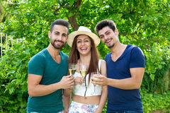 Three laughing friends celebrating with champagne. Royalty Free Stock Photos