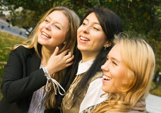 Three laughing girls. Captured outdoors; selective focus Stock Photo