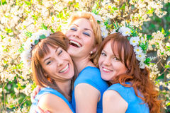 Three laughing girls in blue dresses in the lush garden. Three laughing girls in blue dresses in the lush spring garden Royalty Free Stock Photography