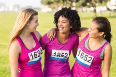 Three laughing runners supporting breast cancer marathon Stock Photos