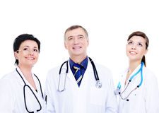 Three laughing successful doctors looking up Royalty Free Stock Image