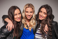 Three laughing young women in leather jackets Stock Photography