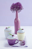 Three lavender cupcakes. With a sea lavender flower in a vase stock photos