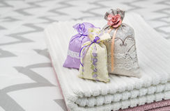 Three lavender scent pouches on towels. Scented sachets on bedroom bed. Fragrance bags for fresh home. Royalty Free Stock Image