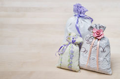 Three lavender scent pouches on wooden board or table. Scented sachets on wood with copy space. Fragrance bags for fresh home. Royalty Free Stock Image