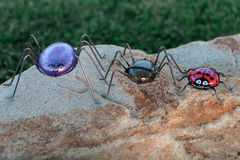 Three lawn art spiders and ladybug Stock Photos
