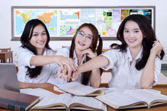 Three learners joining hands in the class Stock Photo