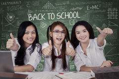 Three learners show thumbs up in the class Royalty Free Stock Image