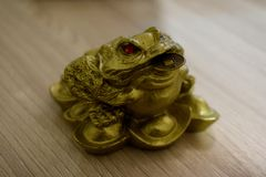 Three-legged money toad with a coin in his mouth. stock image