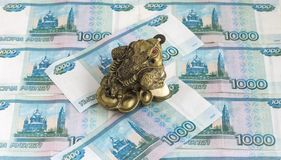 Three-legged money toad Jin Chan as a Chinese symbol of wealth with a coin in his mouth in Russian rubles. Three-legged money toad Jin Chan as a Chinese symbol stock image