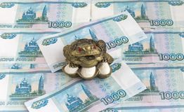 Three-legged money toad Jin Chan as a Chinese symbol of wealth with a coin in his mouth in Russian rubles. Three-legged money toad Jin Chan as a Chinese symbol royalty free stock photography