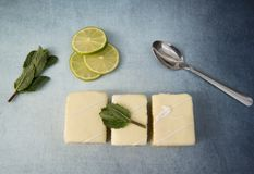 Three lemon cake slices with limes and mint leaves. On a blue background Stock Photos