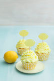 Three lemon cupcakes. Decorated with lemon cupcake toppers stock photography