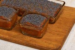 Three lemon poppy cakes on wooden plate Royalty Free Stock Photography