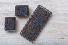 Three lemon poppyseed cakes in glass forms on white wooden table Stock Photography