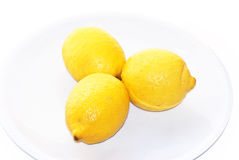 Three lemons. Detail of three isolated and yellow lemons on a white plate Royalty Free Stock Photography