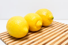 Three lemons on cutting board Royalty Free Stock Image