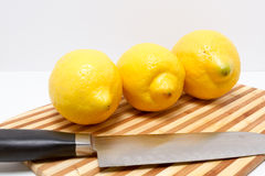 Three lemons on cutting board Stock Photos
