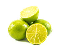Three lemons and limes and one cut in half on a white background Royalty Free Stock Photo