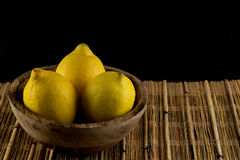 Three lemons in a natural handmade real wood bowl on a bamboo pl Stock Image