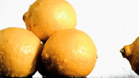 Three lemons in super slow motion being wet stock video