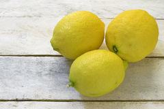 Three lemons on a white wooden table. Stock Image
