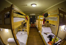 Three-level dormitory beds inside the hostel room for six tourists or students. Three-level dormitory beds inside the hostel room for six tourists or the stock photography