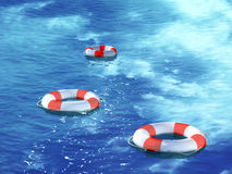 Three lifebuoys, floating on waves Stock Photos