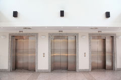 Three lifts with  chromeplated doors in hall Stock Photos