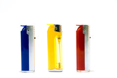 Three lighters. Three cigarette-lighters, red, dark blue and yellow Stock Photography