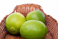Three limes in a basket Royalty Free Stock Image