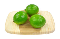 Three Limes On Cutting Board Royalty Free Stock Photos