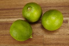 Three limes on a tabletop of acacia wood Stock Photos