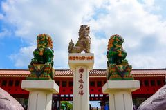 Three Japanese lion statues. Three lion statues in front of the red gate under the cloudy sky royalty free stock photography