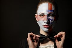 Three Lions Soccer England National Football Team Flag painted on Sports fan face. On black royalty free stock photo