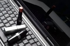 Three lipsticks on a laptop. Three lipsticks on a black laptop Royalty Free Stock Image