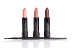 Three lipsticks and makeup brush Royalty Free Stock Photography