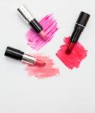 Three lipsticks with swatches on white background.  Stock Photos