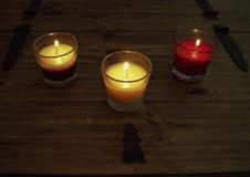 Three lit autumn candles on pine table Royalty Free Stock Image