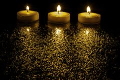 Three candles. Three lit candles on a black background Stock Image